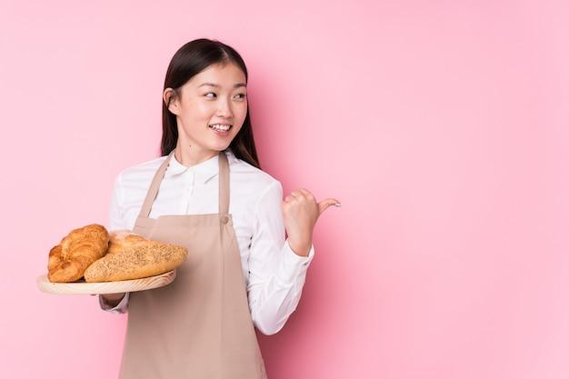 Молодая китайская женщина пекаря изолировала пункты пальцем большого пальца прочь, смеяться и беззаботный.