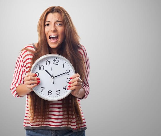 大きな時計を保持している女性のスタジオポートレート