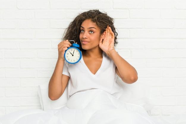 ゴシップを聞いて目覚まし時計を保持しているベッドに座っている若いアフリカ系アメリカ人女性。