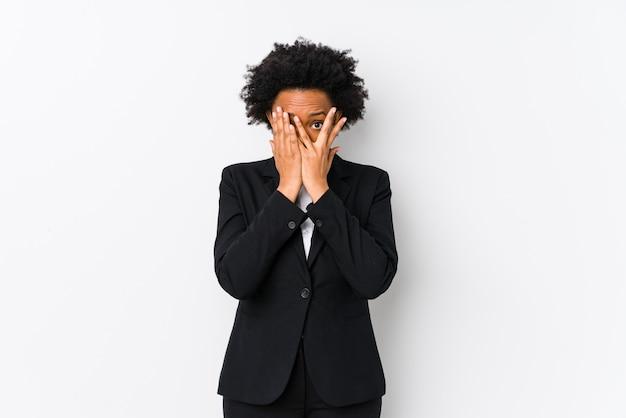 Среднего возраста афро-американских бизнес-леди против белой стены изолированные мигать сквозь пальцы испуганные и нервные.