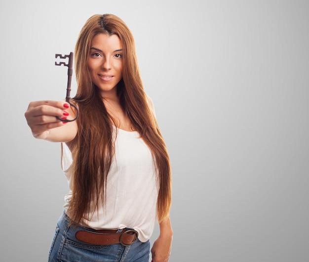 ブルネットの女の子が大きな古い鍵を保持します。