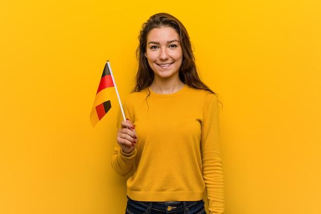 Молодая европейская женщина держит флаг германии счастливым, улыбающимся и веселым.
