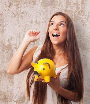 Брюнетка девочка держит желтую копилку