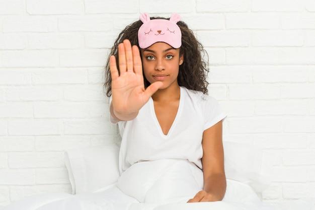 若いアフリカ系アメリカ人の女性が一時停止の標識を示す伸ばした手で立っている睡眠マスクを身に着けているベッドの上に座って、あなたを防ぎます。