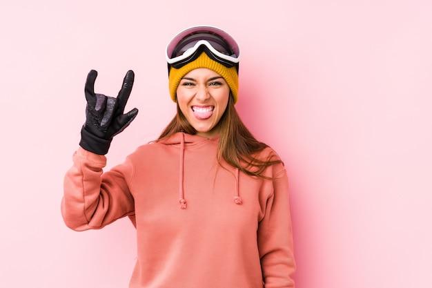 Молодая кавказская женщина нося одежды лыжи изолировала показывать жест рожков как концепция революции.