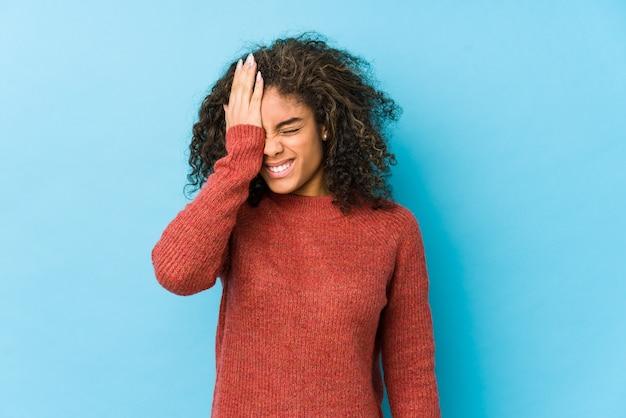 Молодая афро-американская женщина вьющиеся волосы забывая что-то, шлепая лоб с ладонью и закрывая глаза.