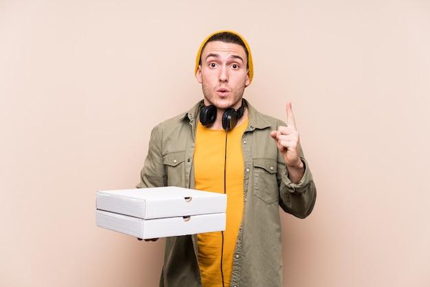 いくつかの素晴らしいアイデア、創造性の概念を持つピザを保持している若い白人男。