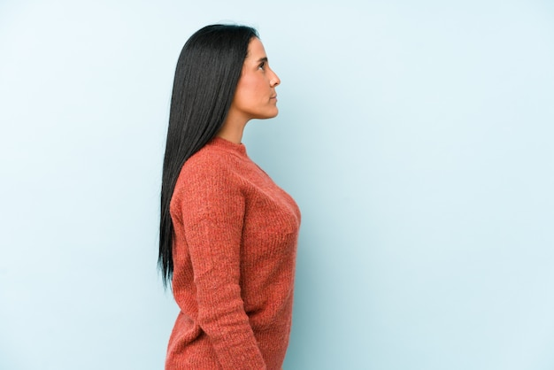 左を見つめる青い壁、横向きのポーズに分離された若い白人女性。
