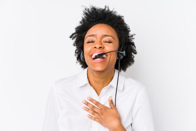 Молодой афроамериканец телемаркетер женщина изолированные смеется громко держать руку на груди.