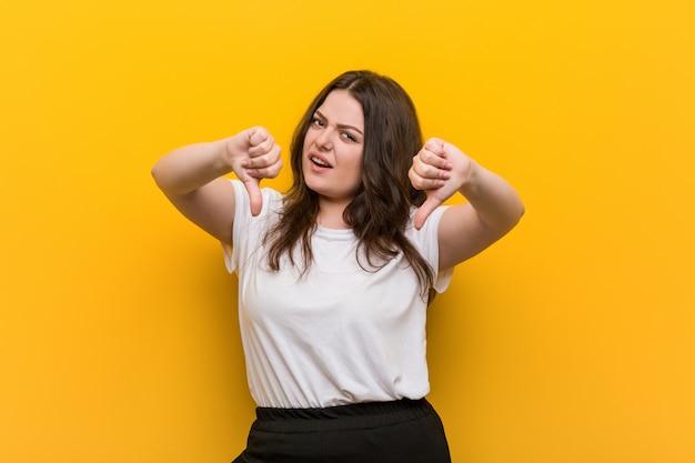 親指を下に示し、嫌悪感を表現する若い曲線のプラスのサイズの女性。
