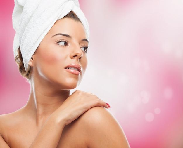 ピンクの背景に、タオルできれいな女性。