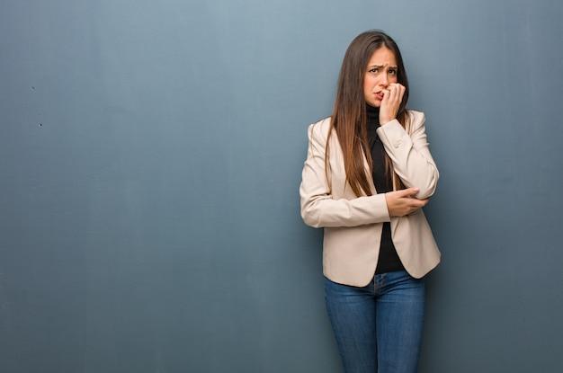 若いビジネス女性の爪をかむ、神経質、非常に心配