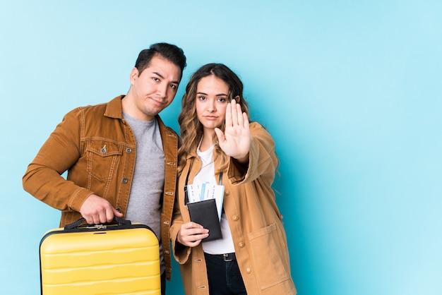 若いカップルが旅行の準備ができて立って、一時停止の標識を示す伸ばした手で立ってあなたを防ぎます。