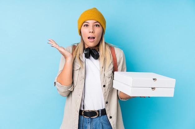 分離されたピザを保持している若い白人女性は驚いてショックを受けた。