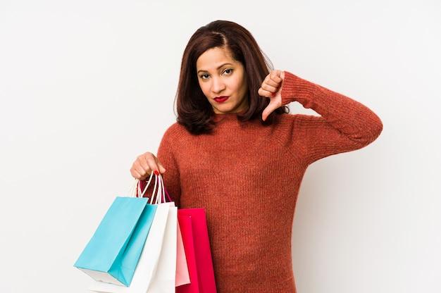 嫌いなジェスチャーを示す分離された買い物袋を保持している中年のラテン女性は親指を下げます。不一致の概念。