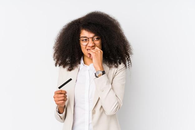 Молодые афро бизнес женщина, держащая кредитный автомобиль изолированы молодые афро бизнес женщина, держащая кредит, прикармливая ногти, нервные и очень тревожно.