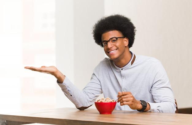 手で何かを保持している朝食を持っている若い黒人男性