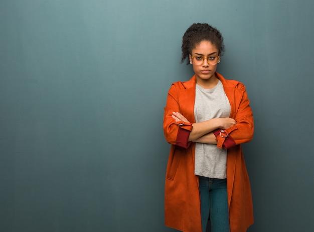 リラックスした腕を交差青い目を持つ若い黒人アフリカ系アメリカ人女性