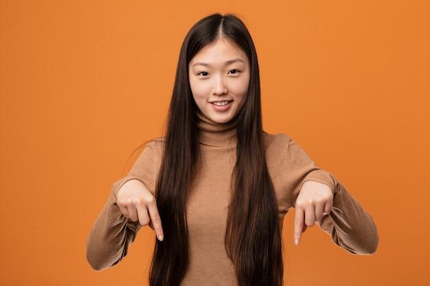 Молодая милая китайская женщина указывает вниз с пальцами, положительным чувством.