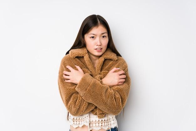 若い中国人女性が白い壁でポーズをとって、低温または病気のために寒くなります。