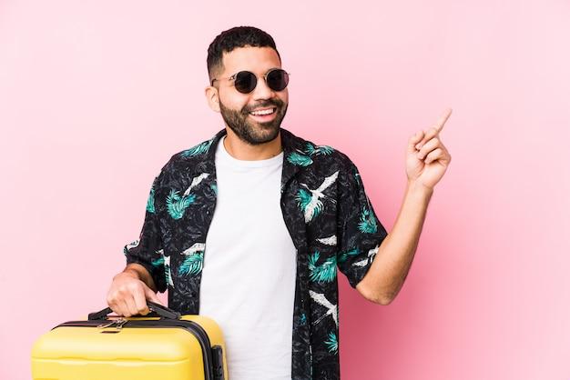 人差し指で元気に指している笑みを浮かべてスーツケースを持って若いラテン男。
