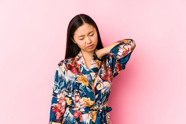 Молодая китайская женщина нося пижаму кимоно изолировала страдая боль шеи из-за сидячего образа жизни.