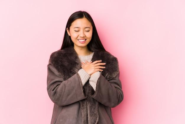 Молодая китайская женщина нося пальто изолировала смеяться над держащ руки на сердце, концепции счастья.