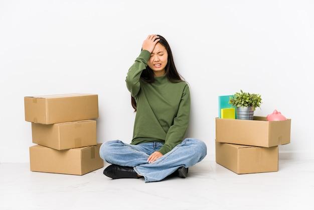 Молодая китайская женщина переезжая в новый дом, забывая что-то, шлепая по лбу ладонью и закрывая глаза.
