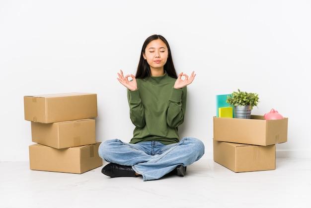 新しい家に移動している若い中国人女性は、懸命に仕事をした後リラックスし、ヨガを行っています。