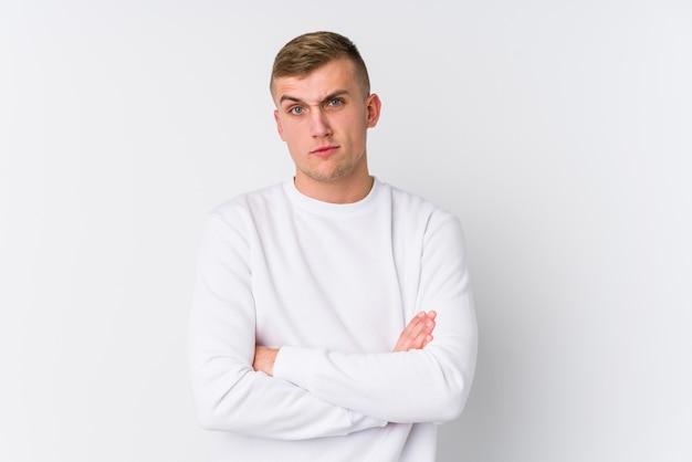 皮肉な表情で見ている不幸な白い壁に若い白人男。