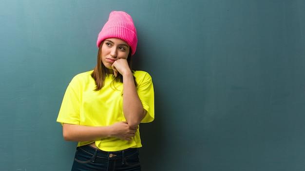 Молодая современная женщина думает о чем-то, глядя в сторону