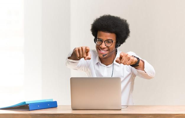 Молодой телепродавец черный человек веселый и улыбающийся, указывая на фронт