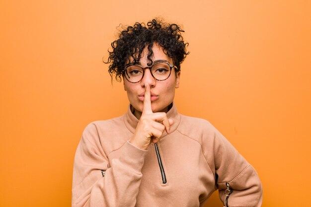 秘密を守るか沈黙を求める茶色の壁に対して若い混合アフリカ系アメリカ人女性。