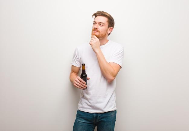 疑って混乱している赤毛の若い男。ビールを保持しています。