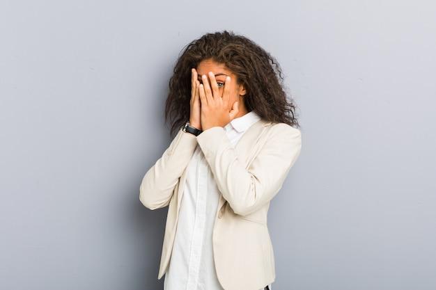 Молодые афро-американских бизнес-леди мигать сквозь пальцы испуганные и нервные.