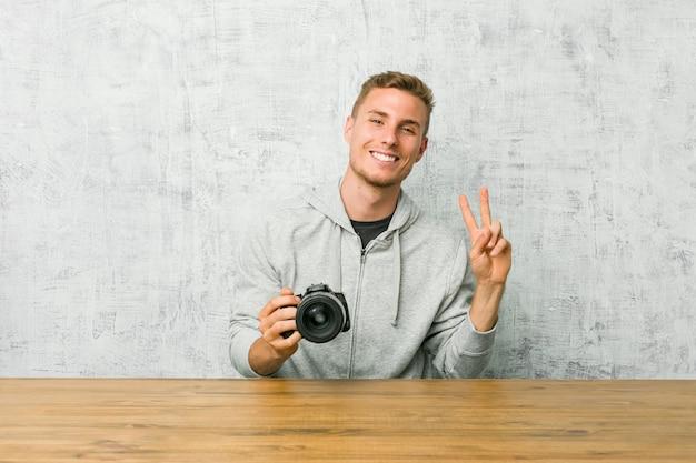 Молодой фотограф держа камеру на таблице показывая номер два с пальцами.