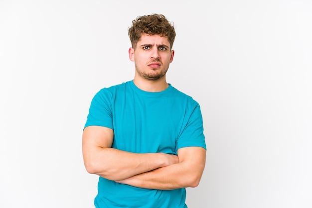 若いブロンドの巻き毛の白人男性は皮肉な表情で不幸な探しています。