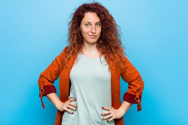 腰に手を保つ自信を持って若い赤毛のエレガントな女性。