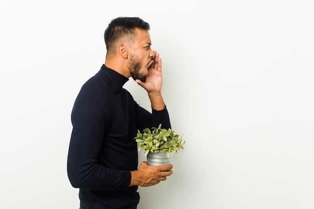 叫び、開いた口の近くの手のひらを保持している植物を保持している若い南アジアの男。