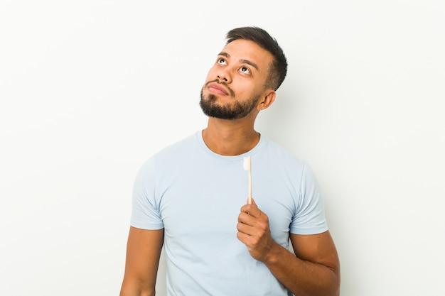 目標と目的を達成することを夢見て歯ブラシを保持している若い南アジアの男