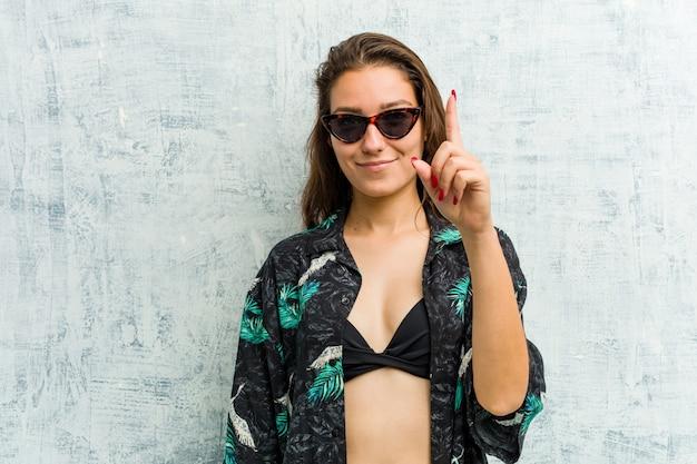 指でナンバーワンを示すビキニを着た若い女性