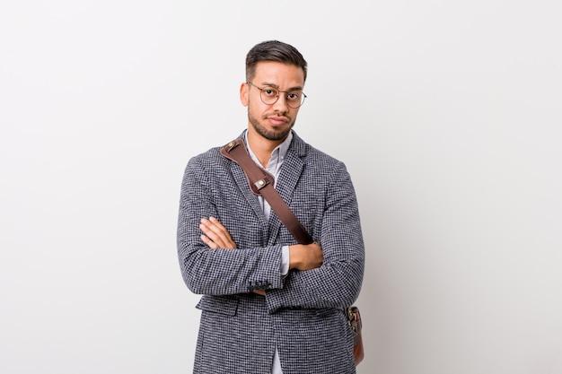 皮肉な表現に不満のある白い壁に若いビジネスマン
