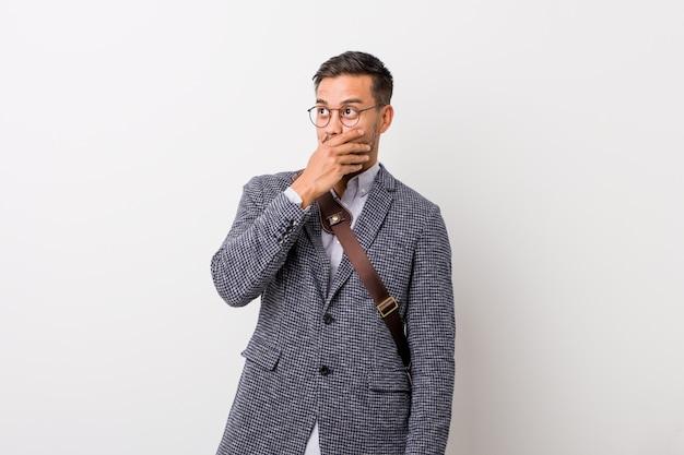 思慮深く見て、手で口を覆っている白い壁に対して若いビジネスマン