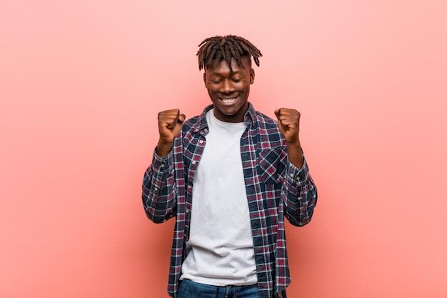 Молодой африканский темнокожий мужчина, поднимающий кулак, чувствующий себя счастливым и успешным. концепция победы.