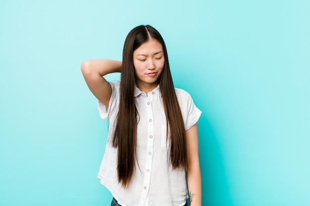 Боль в шее молодой довольно китайской женщины страдая из-за сидячего образа жизни.