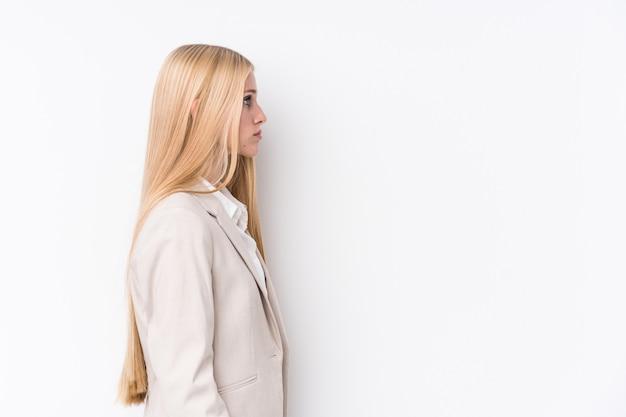 左を見つめる白い壁に若いビジネスブロンドの女性、横ポーズ。