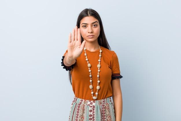 Молодая женщина, стоя с вытянутой рукой, показывая знак остановки