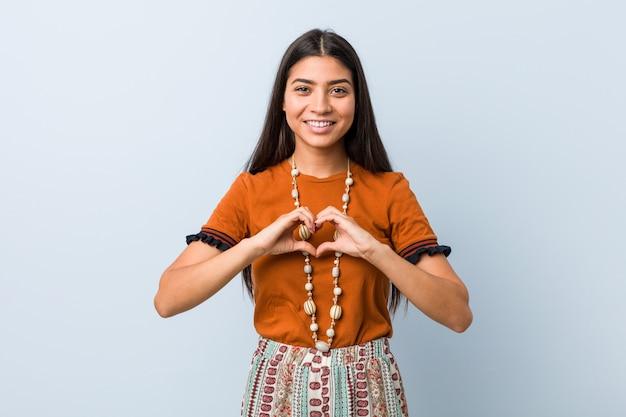 若い女性の笑みを浮かべて、手でハートの形を示す