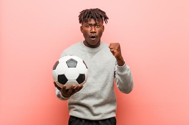 屈託のない、興奮応援サッカーボールを保持している若いフィットネス男