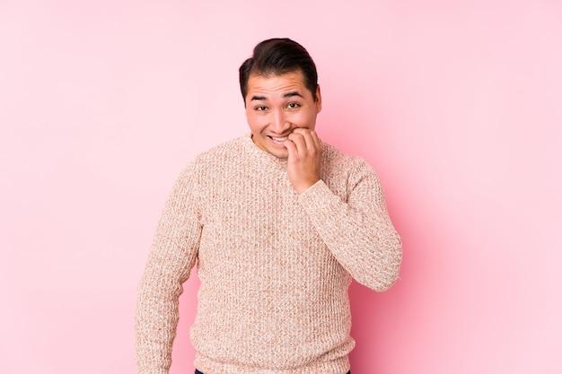 ピンクの壁でポーズをとって若い曲線の男は、爪をかむ、神経質で非常に不安を分離しました。